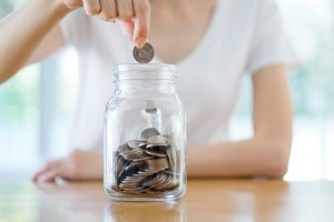 Woman Dropping Coins Into Glass Jar